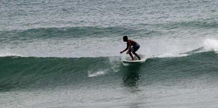Un surfer llegó a eso de las 7:00 de la mañana de hoy hasta la playa Caza y Pesca, en Islote, Arecibo, para practicar el deporte que conoció cuando apenas tenía cinco años. (Para Primera Hora/ Nelson Reyes)