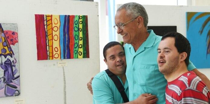 Unos sonrientes Omar Meléndez (24) y Axel Martínez (41), abrazan a Henry Martínez, de la Fundación Puertorriqueña Síndrome Down, al presentar sus obras durante el Simposio de la Familia. (tony.zayas@gfrmedia.com)